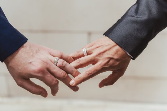 wedding gay couple holding hands with engagement rings