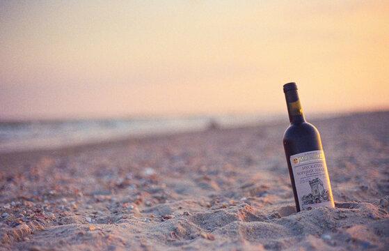 A bottle of Crimean wine on the beach at sunset, a sandy beach.