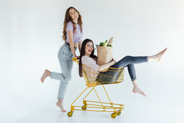 Fototapeta Winsome female models dancing on white background. Indoor photo of two adorable girls posing after shopping.