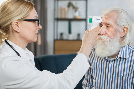 Close up of confident female medical worker, measuring body temperature of male retired patient at home, using forehead contactless infrared thermometer. Coronavirus symptoms.