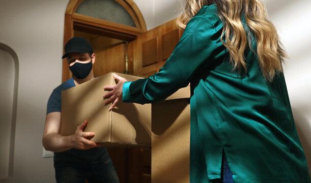 Masked postman in cap delivers cardboard boxes.