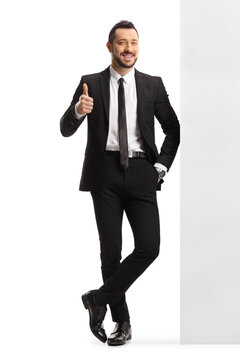 Full length portrait of a young professional man leaning on a wall and showing thumbs up