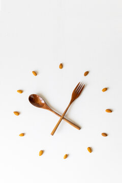 clock, wood spoon and fork clock, bamboo cutlery, almond nuts, almonds, clock on white background lunch time breakfast time, meal time healthy eating, eco-friendly
