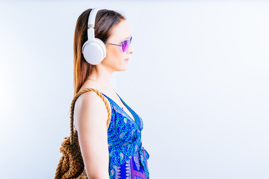 beautiful young woman on white background side view wearing summer glasses listening to music with wireless headphones. concept go on vacation