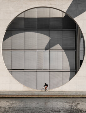 Woman Riding Bicycle By River Against Built Structure