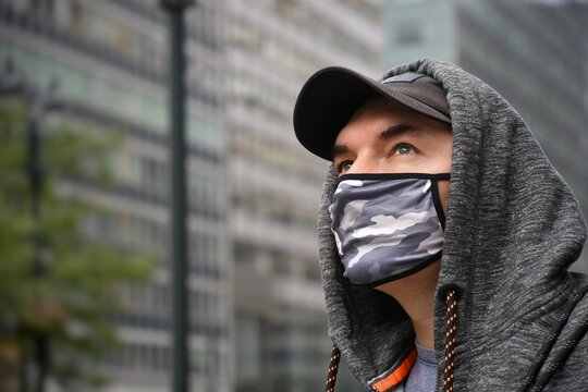 Close-up Of Man Wearing Flu Mask Looking Away While Standing Outdoors