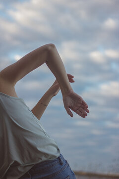 Midsection Of Woman Dancing Against Cloudy Sky