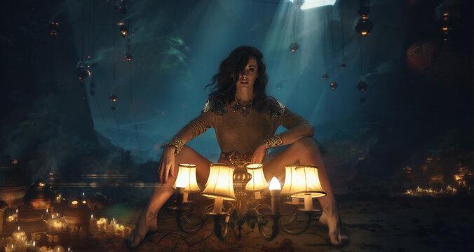 Full Length Portrait Of Woman Sitting By Illuminated Lighting Equipment In Darkroom