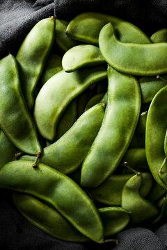 Lima beans pods sitting in a dark grey linen.