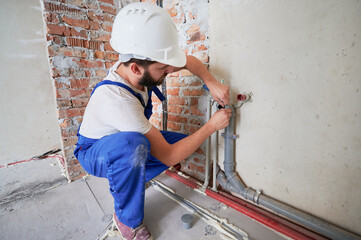 Obraz Man in safety helmet lubricating water pipe to reduce friction and provide long-lasting lubrication. Male plumber in work overalls installing water system in apartment. Plumbing works concept. - fototapety do salonu
