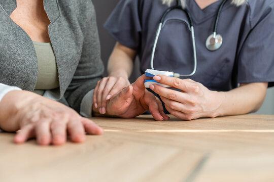 Doctor measuring patients hemoglobin level. Showing usage of finger pulse oximeter