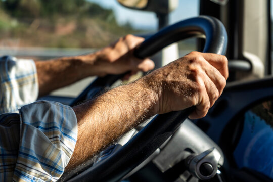 Manos de un conductor profesional en el volante de un vehículo mientras circula por la carretera.