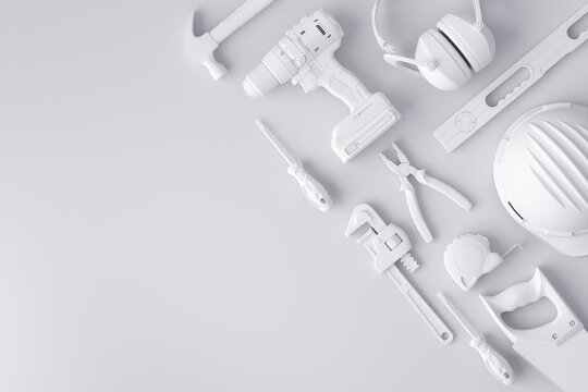 Top view of monochrome construction tools for repair and installation on white