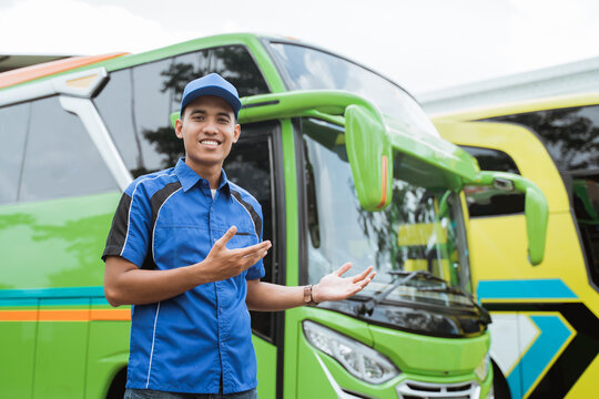 A bus driver in a uniform and a hat with a hand gesture presents something against the background of the bus