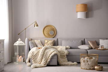 Fototapeta Cozy living room interior with knitted blanket on comfortable sofa