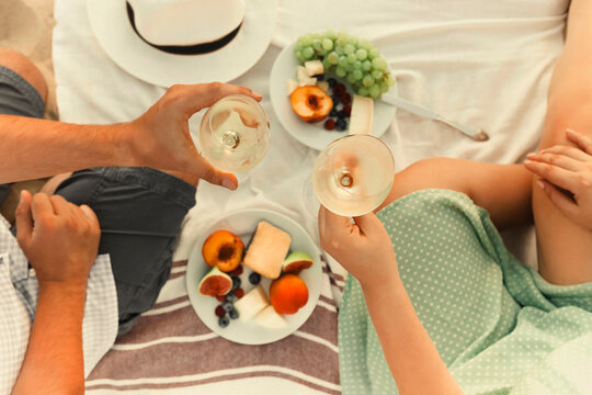 Crop couple drinking wine during picnic