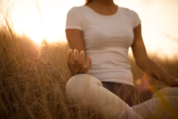 Fototapeta African young woman in nature sitting in yoga position. Focus is on hand.