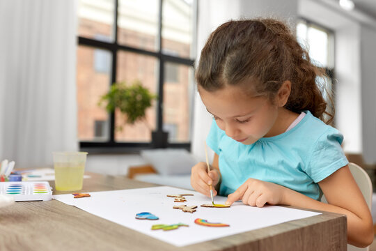 childhood, hobby and leisure concept - little girl with brush painting wooden chipboard items at home