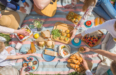 Fototapeta Picnic setting with burgers, tart, croissant, cakes, picnic hamper basket, guitar and food ready for party. Cheerful family sitting on the grass during a picnic in a park. Young smiling family