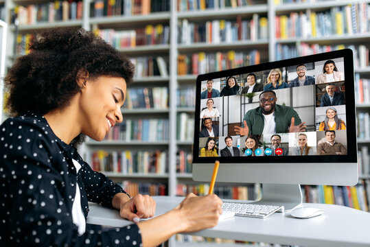 Video call, online education. African American happy female student, learning distantly, watches an online lecture, taking notes, multiracial smiling people on a computer screen, virtual communication