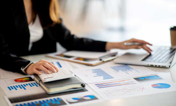 Close up Business woman using calculator and laptop for do math finance on wooden desk, tax, accounting, statistics and analytical research concept