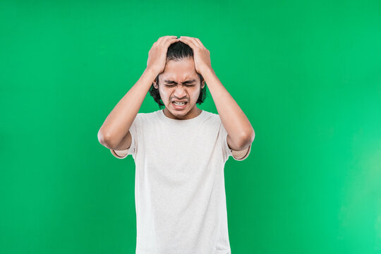 Portrait of stressed Asian man long black hair while holding the head on green background