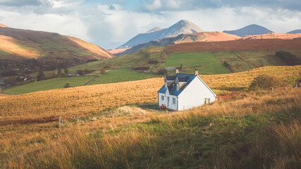 Fototapeta A lone traditional Scottish Highlands white croft house cottage in a rural mountain landscape countryside with Glamaig Peak and the Red Cuillins on the Isle of Skye, Scotland.
