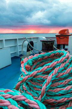 Nautical background. Closeup of an old colorful pink green rope on sunrise with dramatic sky