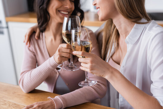cropped view of happy lesbian couple clinking glasses of white wine in kitchen