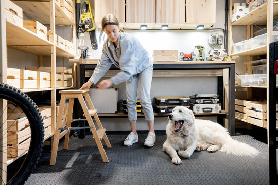 Portrait of a young handywoman sitting with her huge white dog in the home workshop. DIY concept. Motion blurred female
