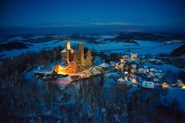 Fototapeta Luftaufnahme von Burg Hanstein und dem Dorf Rimbach im Winter am Abend mit Beleuchtung