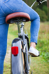 Woman wearing blue jeans sitting on a black bicycle
