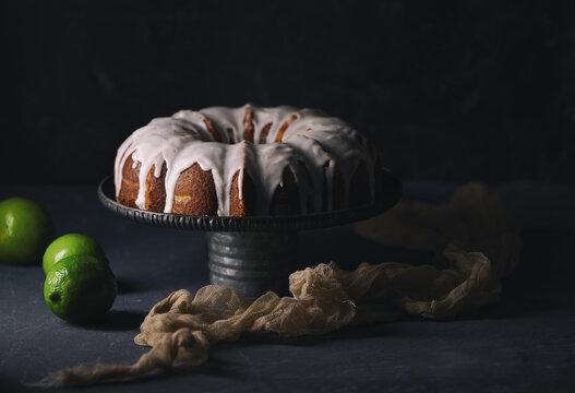 Closeup of a pastry chef slicing a lemon bundt cake with white glaze
