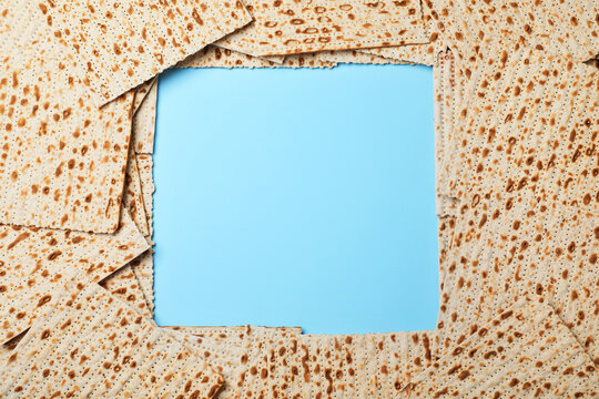 Frame of traditional matzos on light blue background, flat lay. Space for text