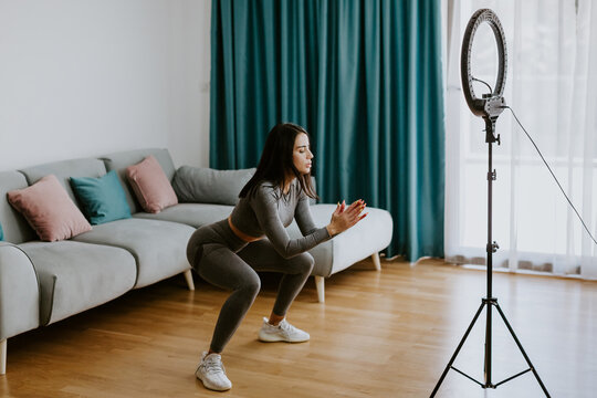 Virtual online fitness. Woman virtual workout at home living room. Fitness stretching exercises online women at home with smartphone. Attractive Woman personal trainer coach recording on camera new