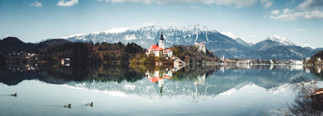 Fototapeta Island in Bled Lake. Charming autumn panorama landscape of island with church rounded colorful trees in the middle of Bled lake. Exciting autumn scene of Bled lake at the sunset.