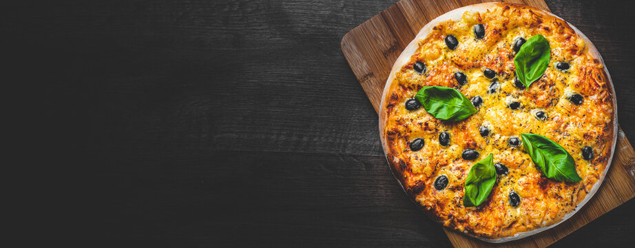 Pizza with Mozzarella cheese, Tomatoes, pepper, olive, Spices and Fresh Basil. Italian pizza. Pizza Margherita or Margarita on wooden table background