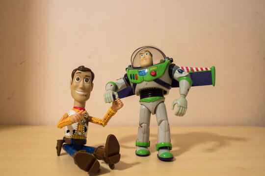 AVOLA, ITALY - Mar 21, 2021: Woody and Buzz Lightyear toys holding their hands