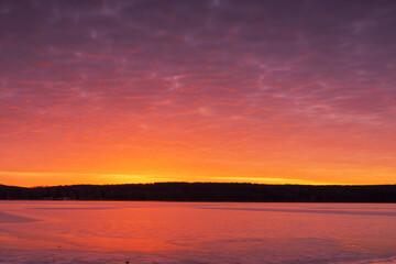 Prachtig zonsonderganglandschap met oranje-paarse lucht weerspiegeld in het water