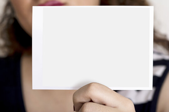 Young woman holding a sonography image editable mock-up series template in hand in front of her face