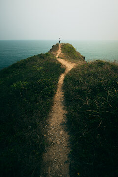 Vertical shot of a narrow walkway on the cliff peak leading to the edge of the sea