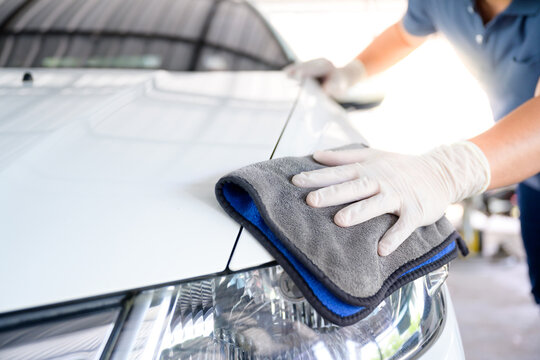 Car wash service personnel clean their cars with microfiber cloths. Details and valet concept Selective focus Close-up view