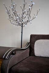 Zdjęcie wnętrza przedstawiające sofę z lampą w kształcie drzewa