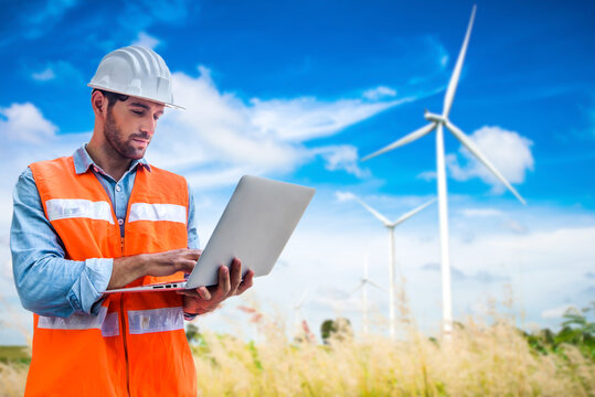 Engineering man using laptop to checking wind turbine generator of electricity at outdoor, blue sky and cloudy background
