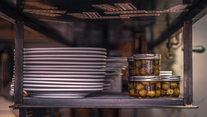 White dinner plates and jars stacked up on top shelf of a kitchen Wall mural