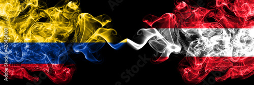 Colombia, Colombian vs Austria, Austrian smoky mystic flags placed side by side. Thick colored silky abstract smokes flags.