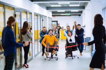 Friendly work team  ride chairs in office room cheerfully excited diverse employees laugh while...