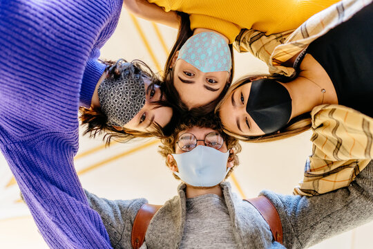 Group of four teenagers students looking down arm in arm wearing protective mask. Friends looking at camera and laughing hugging each other wearing bright colorful clothes in covid-19 pandemic period