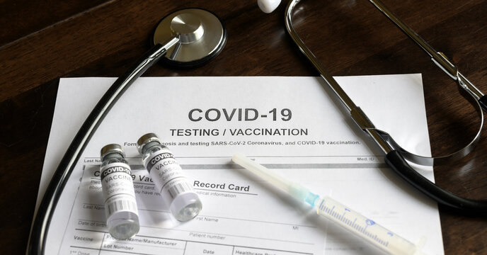 Coronavirus vaccine and test form on desk in clinic, COVID-19 vaccination concept