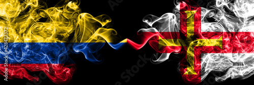 Colombia, Colombian vs United Kingdom, Great Britain, British, Guernsey  smoky mystic flags placed side by side. Thick colored silky abstract smokes flags.